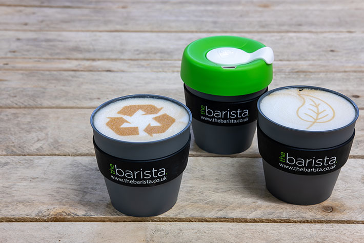 Reusable coffee cups with recycling icons in coffee foam