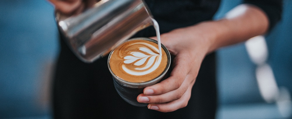 barista pouring a coffee heart
